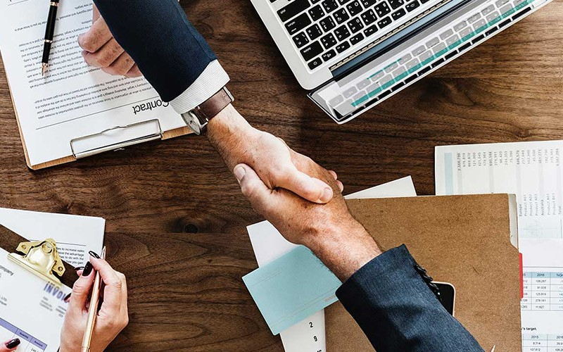 Best HR - Two Business People Shaking Hands Over Desk